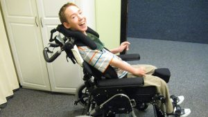 Smiling Young Man in Seating Dynamics Wheelchair